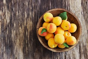 ripe apricots in a wooden bowl