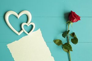 Red rose on blue wooden background