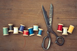 Scissors and wooden spools of thread