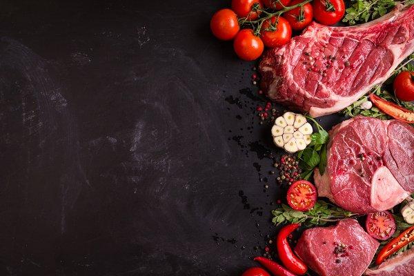Raw meat steaks on a dark backgroun…