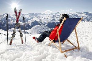 Women at mountains lies sun-lounger