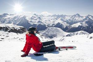 Girl skier lying on snow with ski