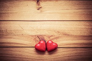 Couple of red hearts on wood.