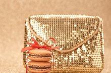 Macarons. Shiny gold handbag, bokeh