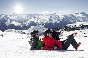 Skiers lying on snow in mountains