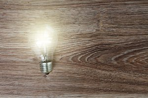 Illuminated light bulb on wood