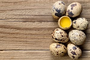 Quail eggs on wooden table top view