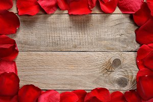 Red rose petals on wooden table