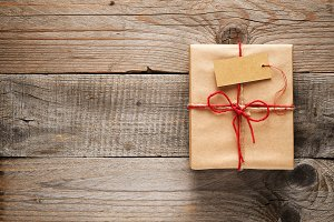 Gift box with tag on wooden table