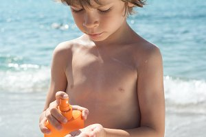 Boy applies sunscreen in his hand