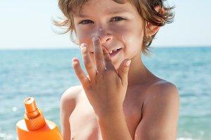 child apply sun cream on his nose
