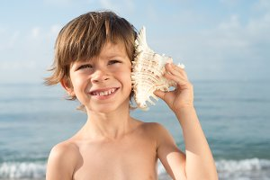 child listening conch at beach