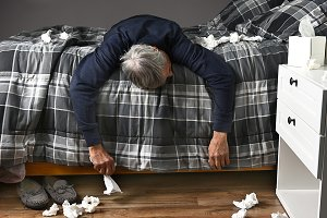 Sick Man Lying Across Bed