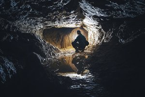 Man in cave with limestone formation