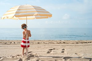 child on the beach under umbrella