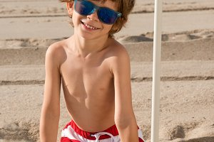 child on the beach with sunglasses