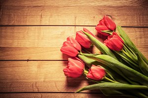Red tulip flowers on wood.