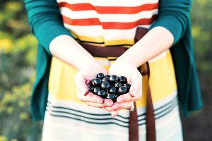 Girl holding a black currant