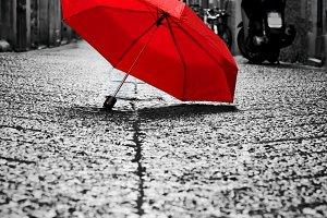 Red umbrella on cobblestone street.