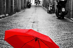 Red umbrella on cobblestone street.