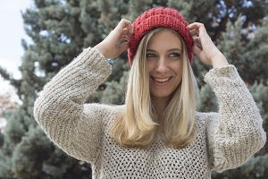 Blonde woman in winter, smiling.