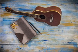 Ukulele with note book and pencil