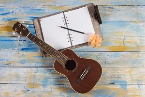 Ukulele with notebook and pencil