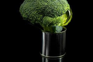 broccoli on a tin can over black
