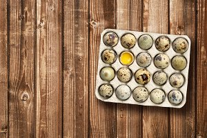 Quail eggs in tray on wooden table