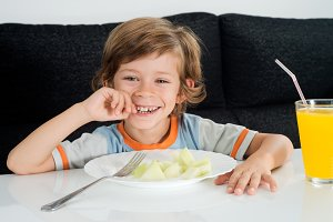 boy smiling with juice and fruit