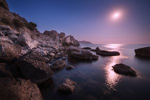 Rocks on the sea with moon at night