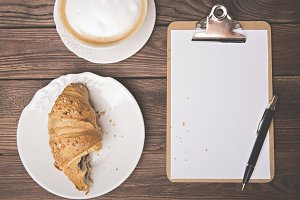 Notebook, pen and cup of croissant.
