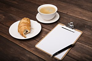 Notebook with a pen, cappuccino