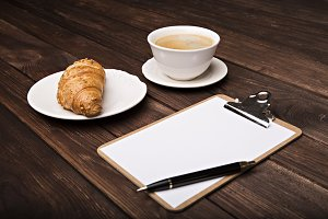 coffee and croissant next to notepad