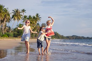 Happy children dancing on the beach