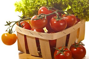 Tomatoes and salad in  wooden basket