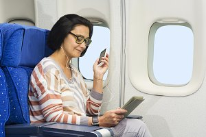 passenger in plane with smart device