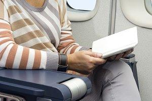 passenger in plane using tablet