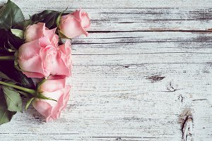 Pink roses on textured wooden table