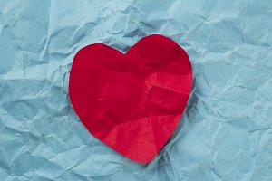 Red heart on blue paper