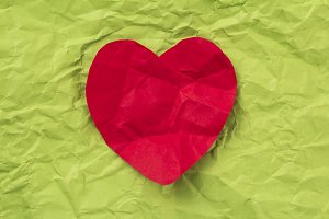 Red heart on green paper