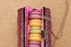 Macarons in fashion handbag on gold