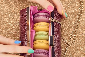 Macarons in fashion handbag on gold