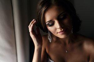 Brunette bride near the window
