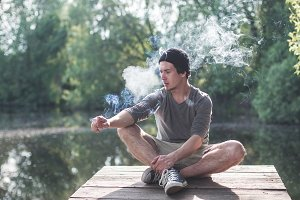 man smokes near the lake