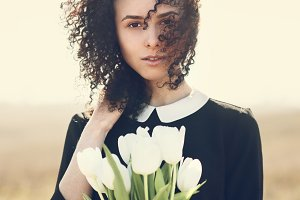 curly-haired girl with white tulips