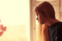 girl is sad at the window