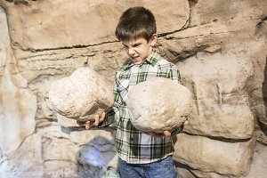Strong child holds heavy stones.
