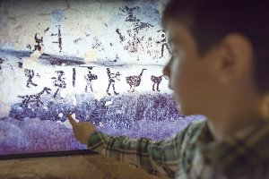 Child looks at ancient mural