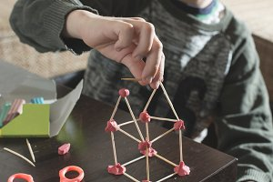 Child make house with wooden sticks